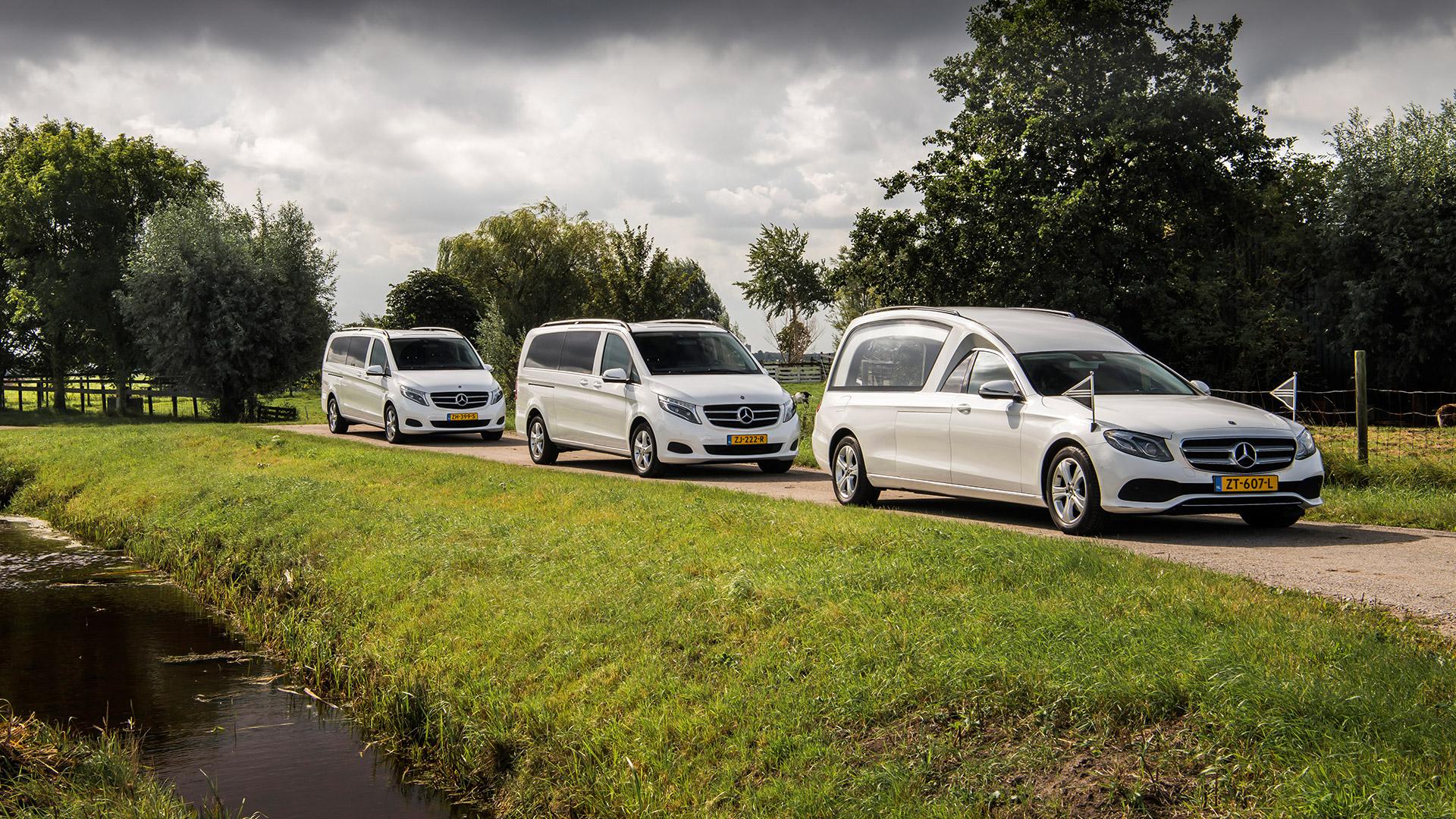 Moderne witte rouwstoet bestaande uit een witte Mercedes begrafenisauto en twee luxe V-klasse volgauto's die de overledene en nabestaanden vervoeren naar de begrafenis, crematie of uitvaart.