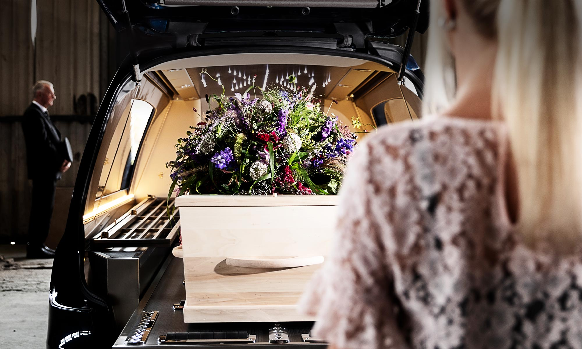Uitvaartkist en rouwboeket in blauwe Mercedes rouwauto met sterrenhemel.